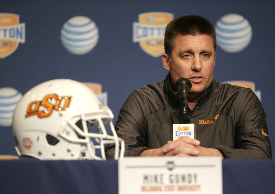 Photo -  Oklahoma State coach Mike Gundy answers questions from reporters during the AT&T Cotton Bowl Classic media day on Monday, Dec. 30, 2013, in Arlington, Texas.   Missouri will play Oklahoma State in the annual bowl game on Friday. (AP Photo/Tim Sharp)