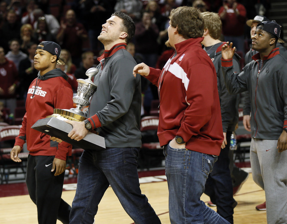 Photo - OU football player Blake Bell carries the Sugar Bowl trophy as football players walk to half court before addressing fans at halftime during an NCAA men's college basketball game between Baylor and the University of Oklahoma (OU) at Lloyd Noble Center in Norman, Okla., Saturday, Feb. 8, 2014. Photo by Nate Billings, The Oklahoman