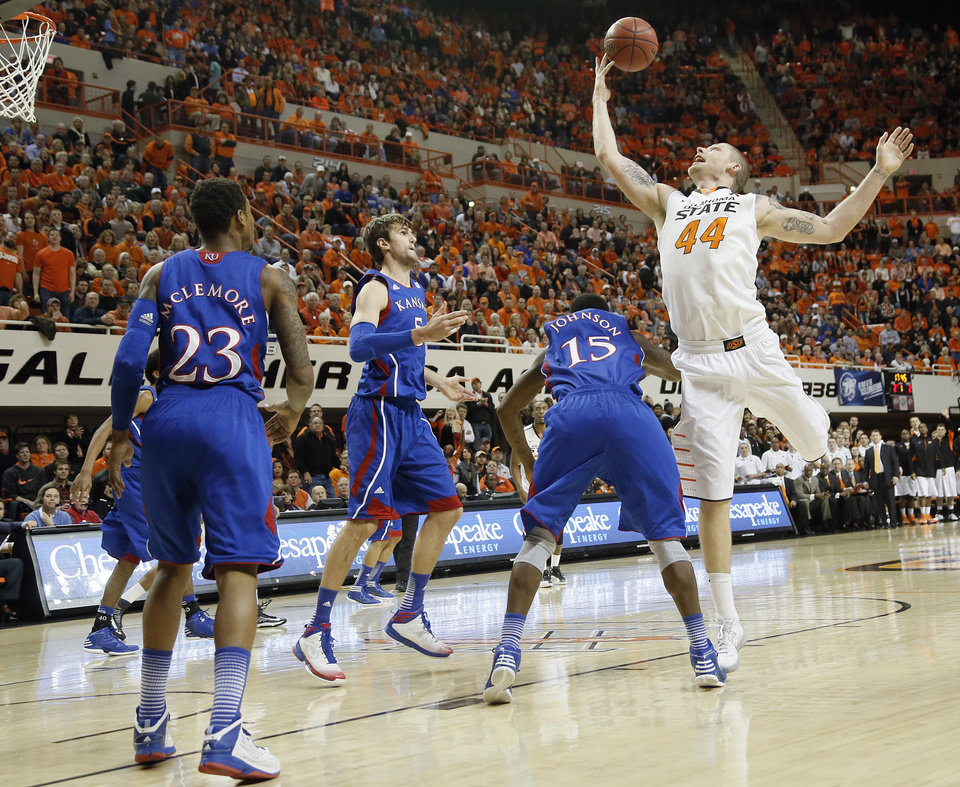 Photo - Oklahoma State 's Philip Jurick (44) pulls in a rebound over Kansas' Elijah Johnson (15) during the college basketball game between the Oklahoma State University Cowboys (OSU) and the University of Kansas Jayhawks (KU) at Gallagher-Iba Arena on Wednesday, Feb. 20, 2013, in Stillwater, Okla. Photo by Chris Landsberger, The Oklahoman