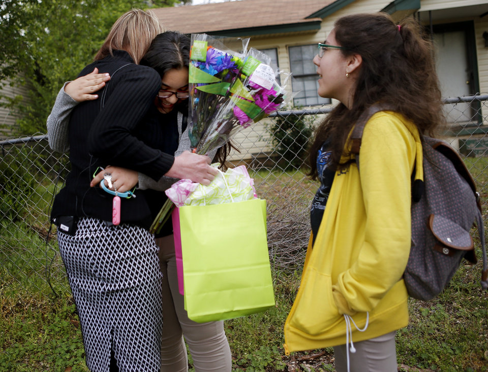 Photo -  Oklahoma City Police dispatcher Barbara Jones hugs Andrea Gonzalez, 14, on Wednesday outside her Oklahoma City home. Jones helped keep Andrea and her sister calm until police could arrive during a burglary at their home last week. [Photo by Bryan Terry, The Oklahoman]