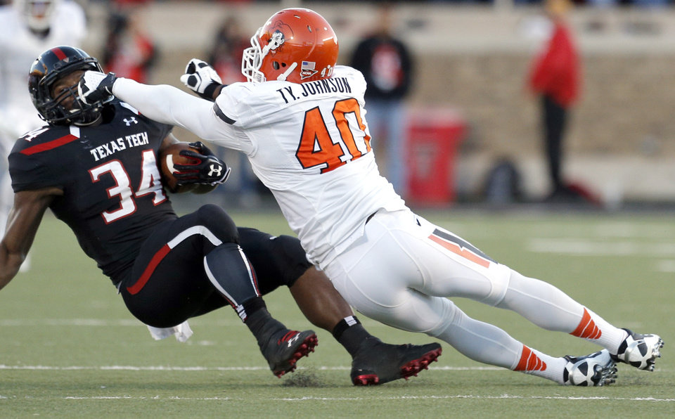 Oklahoma State \'s Tyler Johnson (40) tackles Texas Tech\'s Kenny Williams (34) during the college football game between the Oklahoma State Cowboys (OSU) and the Texas Tech Red Raiders (TTU) at Jones AT&T Stadium in Lubbock, Texas, Saturday, Nov. 2, 2013. Photo by Sarah Phipps, The Oklahoman