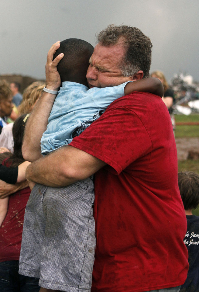 """Big Dog""; Jim Routon hugs young neighbor Hezekiah ""Little Dog"" Darbon at Briarwood Elementary School on Monday after a tornado ripped through the area near SW 149 and Hudson. BY PAUL HELLSTERN, THE OKLAHOMAN )"