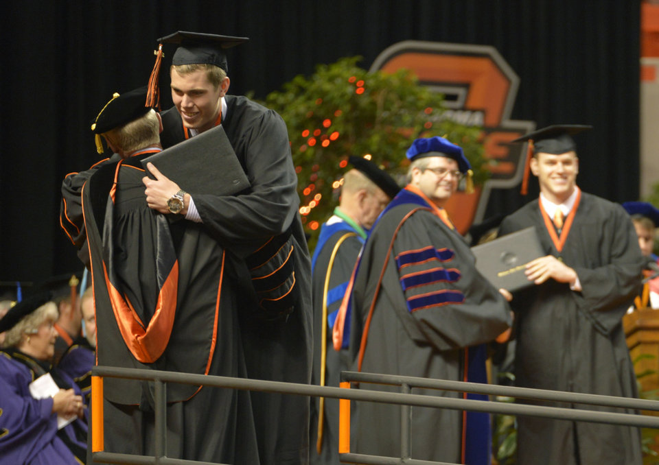Photo -  Above: Oklahoma State University gradate Mason Cox hugs President Burns Hargis after recieving his diploma during the May 2014 commencement ceremony. The Oklahoman Archives   Jackie Dobson