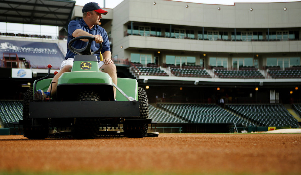 Photo - Monte McCoy, head groundskeeper of the Oklahoma City RedHawks, checks the field at Chickasaw Bricktown Ballpark.  Photo by Bryan Terry, The Oklahoman