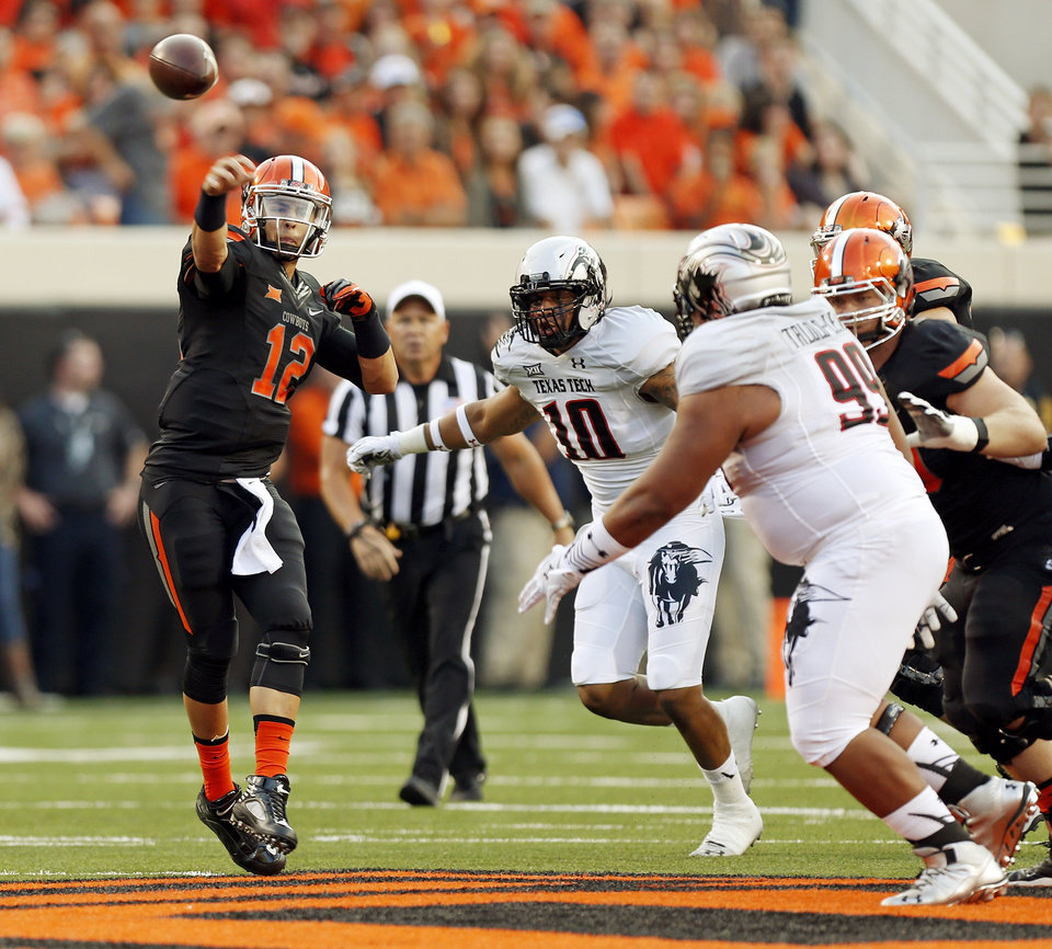 Photo - Oklahoma State's Daxx Garman (12) passes during a college football game between the Oklahoma State Cowboys (OSU) and the Texas Tech Red Raiders at Boone Pickens Stadium in Stillwater, Okla., Thursday, Sept. 25, 2014. Photo by Nate Billings, The Oklahoman