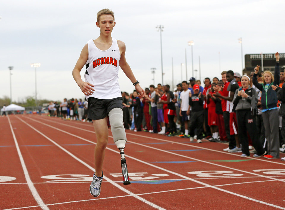 Photo - Athletes, coaches and spectators line the track as Norman's Patrick Ahearn finishes the 400-meter dash with his prosthetic leg during a track meet at Putnam City High School in Oklahoma City, Friday, April 5, 2013. Ahearn lost part of his leg in a personal watercraft accident last year. Photo by Nate Billings, The Oklahoman