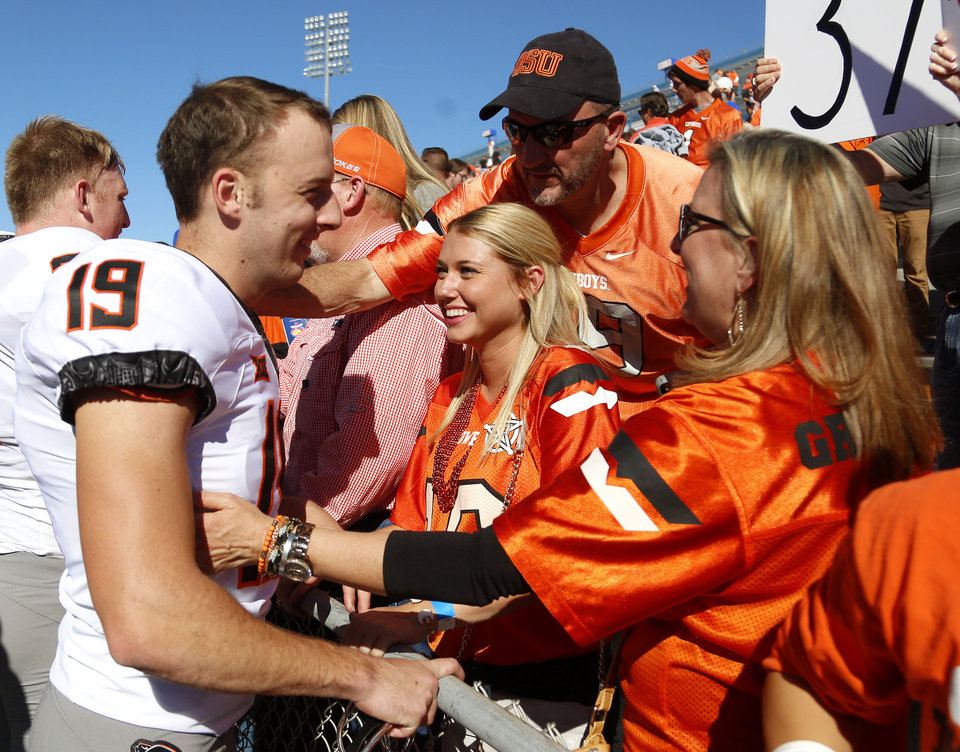 Photo -  Oklahoma State kicker Ben Grogan celebrates with his mom, Marcia Grogan, right, girlfriend, Payton Jones, center, and dad Mike Grogan after the Cowboys' game vs. Kansas on Saturday. Grogan set the school's all-time scoring record. [PHOTO BY SARAH PHIPPS, The Oklahoman]
