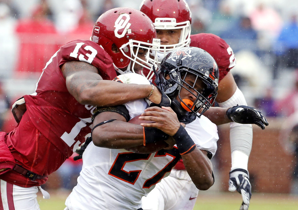 Photo - Oklahoma's Ahmad Thomas (13) tackles Oklahoma State's Justice Hill (27) during the Bedlam college football game between the Oklahoma Sooners (OU) and the Oklahoma State Cowboys (OSU) at Gaylord Family - Oklahoma Memorial Stadium in Norman, Okla., Saturday, Dec. 3, 2016. Photo by Steve Sisney, The Oklahoman