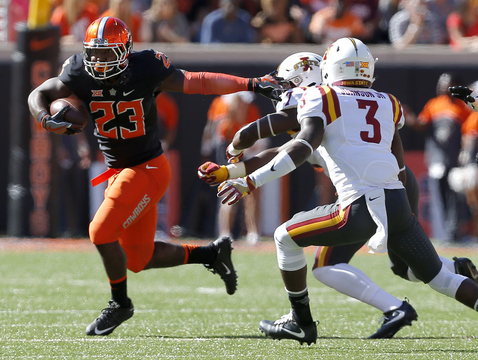 Photo - Oklahoma State's Rennie Childs (23) rushes as Iowa State's Willie Harvey (7) and Mike Johnson (3) defend during a college football game between the Oklahoma State University Cowboys (OSU) and the Iowa State University at Boone Pickens Stadium in Stillwater, Okla., Saturday, Oct. 8, 2016. Photo by Sarah Phipps, The Oklahoman