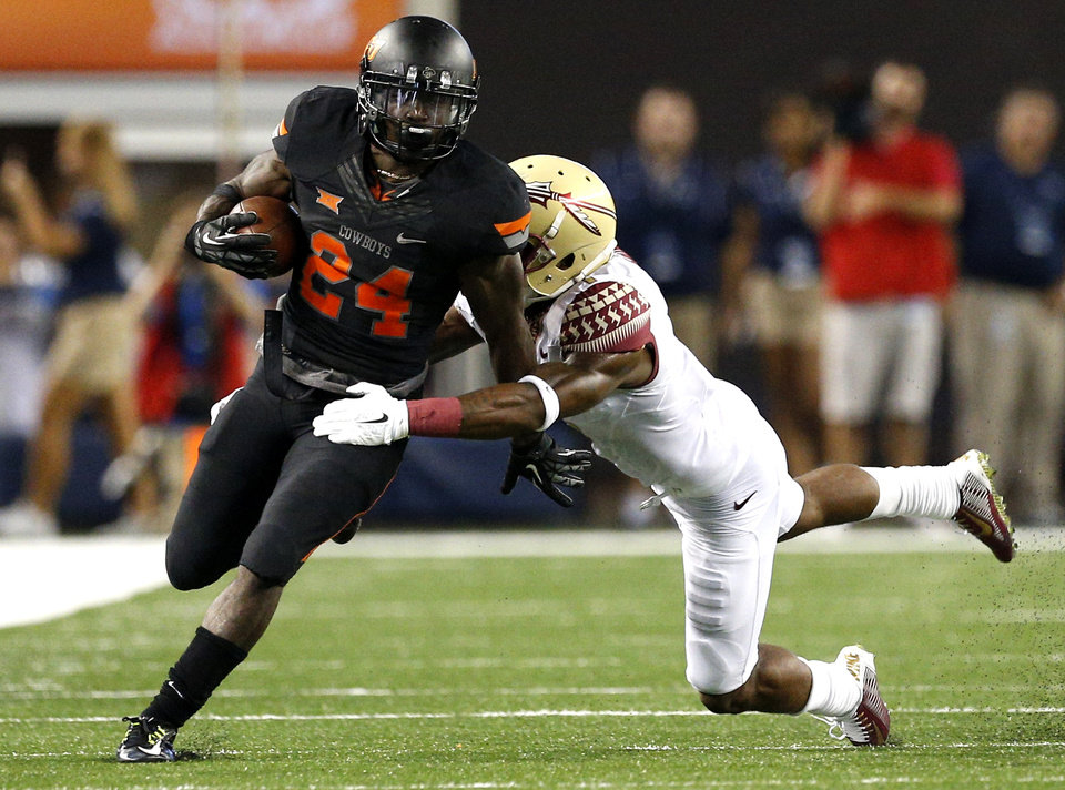 Photo - Oklahoma State's Tyreek Hill (24) tries to get by Florida State's Tyler Hunter (1) during the college football game between Oklahoma State University (OSU) and Florida State University (FSU) at the AdvoCare Cowboys Classic at At&T Stadium in Arlington, Texas,  Saturday, Aug. 30, 2014. Photo by Sarah Phipps, The Oklahoman