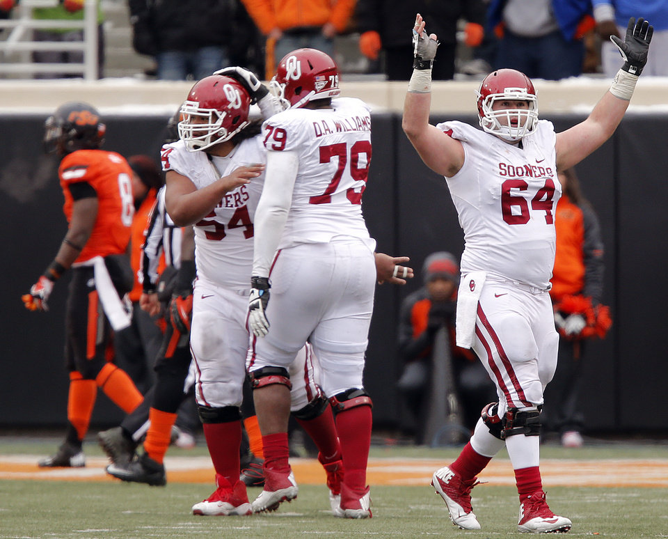 Photo - Oklahoma's Gabe Ikard (64) celebrates after a touchdown that put the Sooners up for good over the Cowboys during the Bedlam college football game between the Oklahoma State University Cowboys (OSU) and the University of Oklahoma Sooners (OU) at Boone Pickens Stadium in Stillwater, Okla., Saturday, Dec. 7, 2013. Photo by Chris Landsberger, The Oklahoman