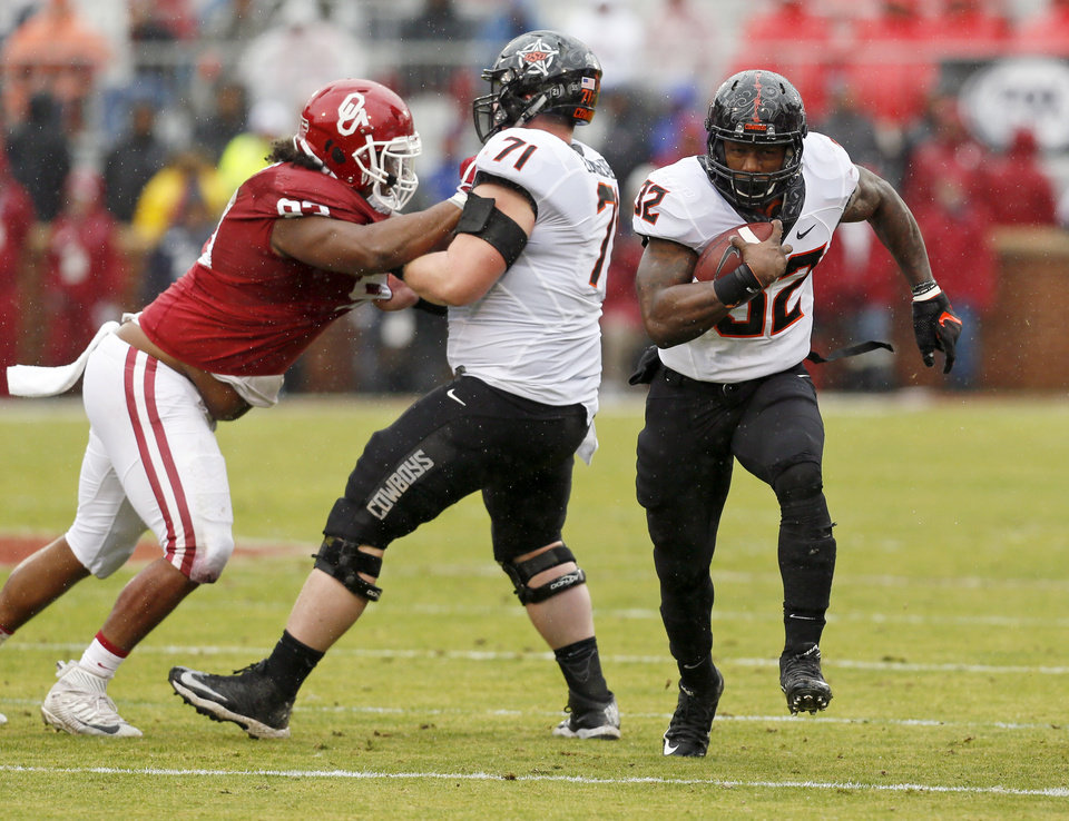 Photo - Oklahoma State's Chris Carson (32) carries the ball as Brad Lundblade (71) blocks Jordan Wade (93) during the Bedlam college football game between the Oklahoma Sooners (OU) and the Oklahoma State Cowboys (OSU) at Gaylord Family - Oklahoma Memorial Stadium in Norman, Okla., Saturday, Dec. 3, 2016. Photo by Nate Billings, The Oklahoman