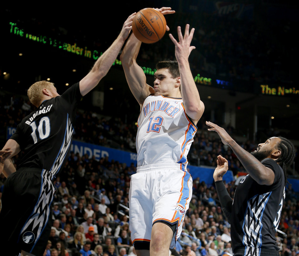 Oklahoma City's Steven Adams (12) goes for a rebound between Minnesota's Chase Budinger (10) and Dante Cunningham (33) during an NBA basketball game between the Oklahoma CIty Thunder and the Minnesota Timberwolves at Chesapeake Energy Arena in Oklahoma City, Wednesday, Feb. 5, 2014. Photo by Bryan Terry, The Oklahoman