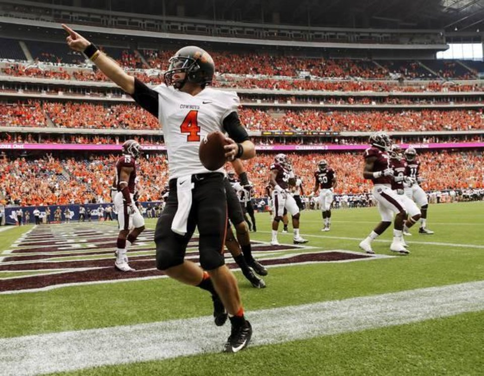 Oklahoma State\'s J.W. Walsh (4) celebrates a touchdown run in the second quarter during the AdvoCare Texas Kickoff college football game between the Oklahoma State University Cowboys (OSU) and the Mississippi State University Bulldogs (MSU) at Reliant Stadium in Houston, Saturday, Aug. 31, 2013. Photo by Nate Billings, The Oklahoman