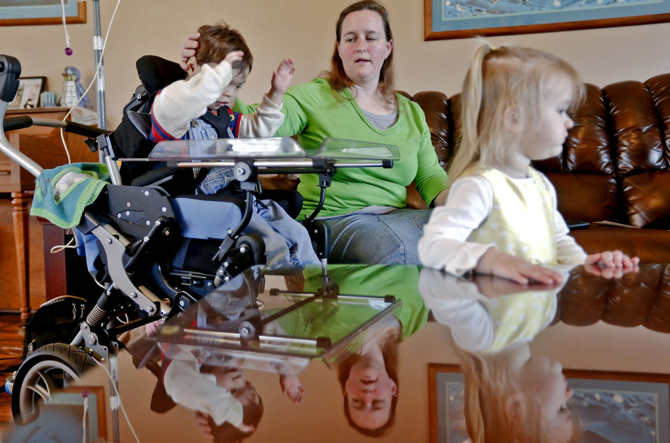 Photo - Ashley Zeno sits with her son Joey and daughter Caitlyn at their home Monday in Mustang.  Photos by Chris Landsberger, The Oklahoman