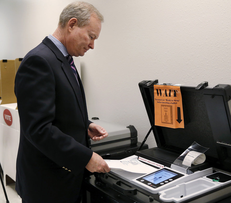 Photo - Oklahoma City Mayor Mick Cornett inserts his ballot into a voting machine  after he voted. Early voters at Oklahoma County  Election Board, 4201 N Lincoln Blvd. ,on Thursday, Feb. 27, 2014.       Photo by Jim Beckel, The Oklahoman