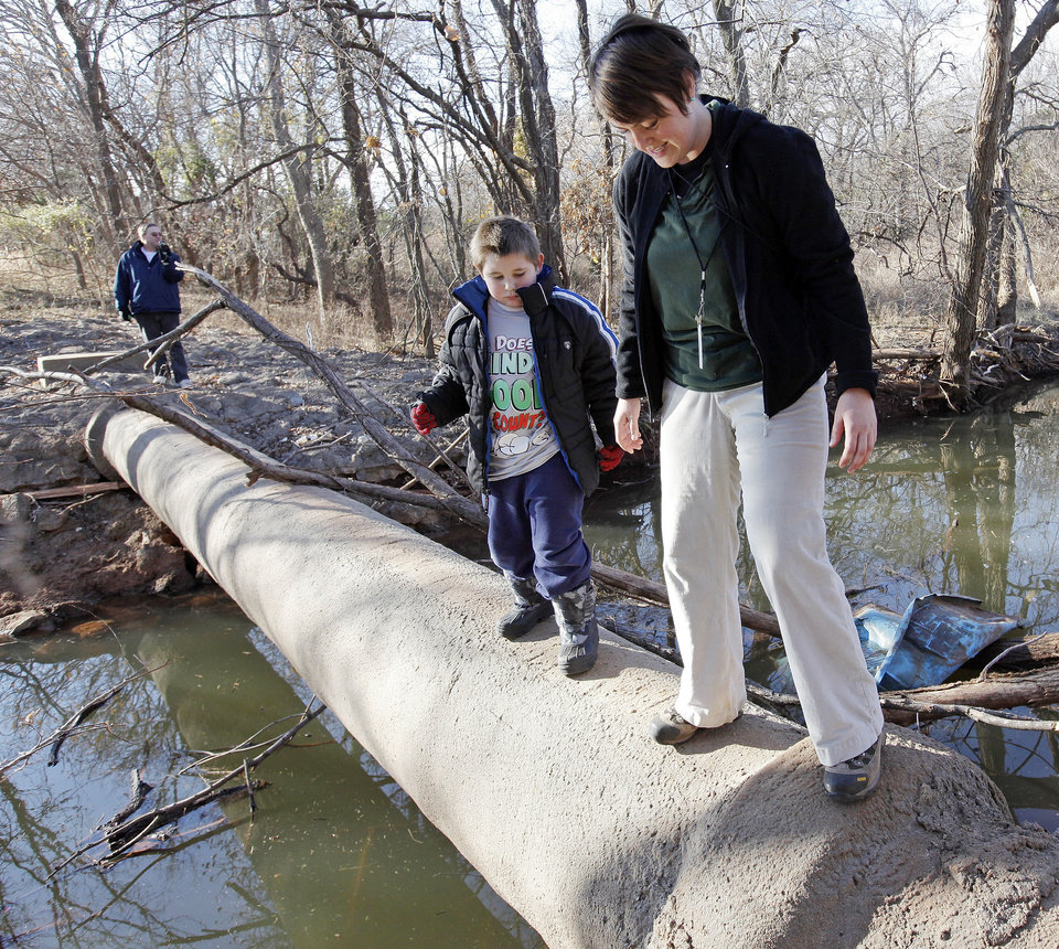 Naturalist Casey Lindo, right, and Zachary Miller cross a creek at Martin Park Nature Center. Much of the park is not accessible to people with disabilities. PHOTO BY NATE BILLINGS, the OKLAHOMAN ARCHIVEs