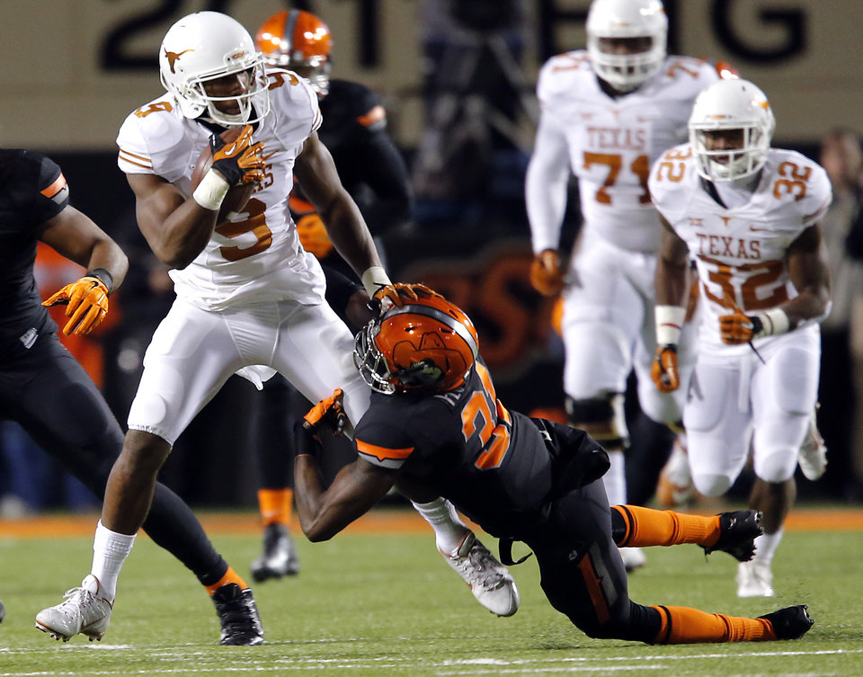Photo - Texas' John Harris (9) pushes off a tackle by Oklahoma State's Tre Flowers (31) during the college football game between the Oklahoma State University Cowboys (OSU) the University of Texas Longhorns (UT) at Boone Pickens Staduim in Stillwater, Okla. on Saturday, Nov. 15, 2014.  Photo by Chris Landsberger, The Oklahoman