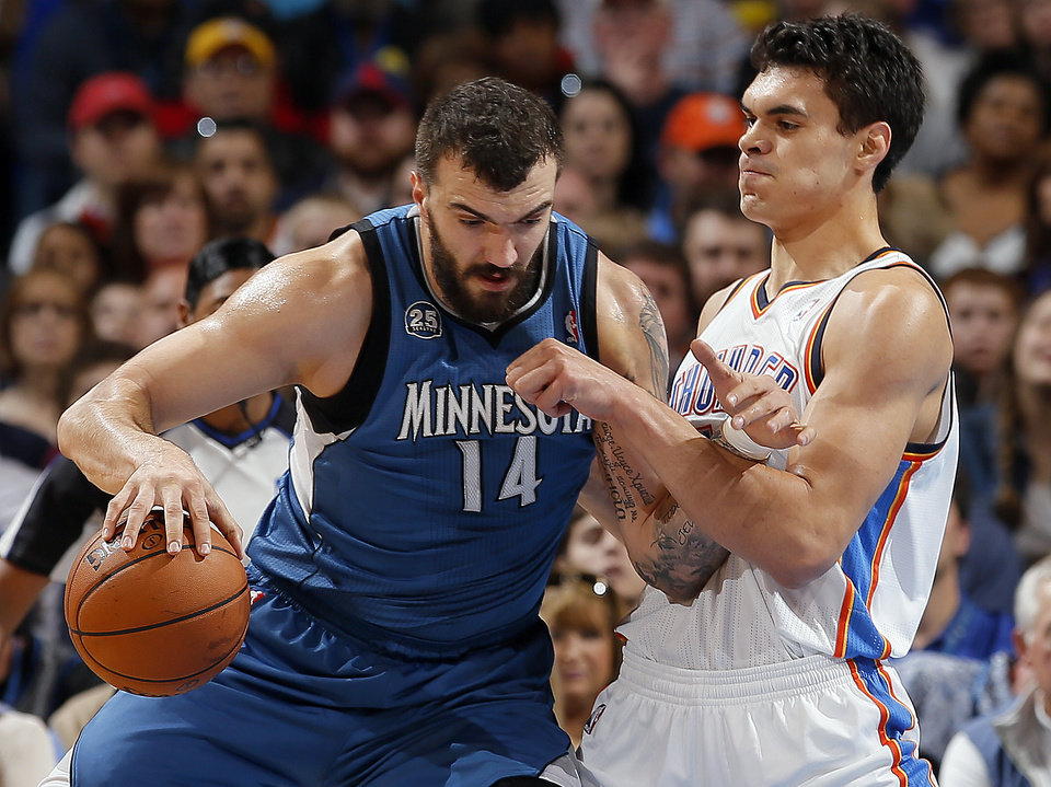 Photo - Oklahoma City's Steven Adams (12) defends against Minnesota's Nikola Pekovic (14) during the NBA game between the Oklahoma City Thunder and the Minnesota Timberwolves at the Chesapeake Energy Arena, Sunday, Dec. 1, 2013. Photo by Sarah Phipps, The Oklahoman