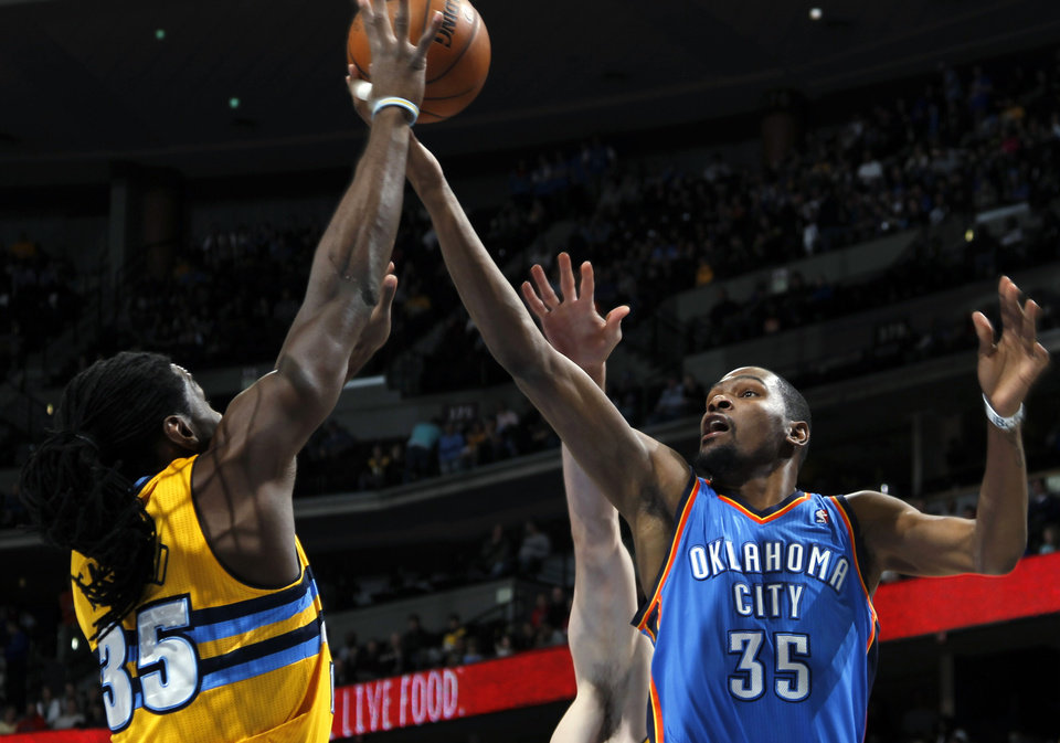 Denver Nuggets forward Kenneth Faried, left, reaches to block a shot by Oklahoma City Thunder forward Kevin Durant in the first quarter of an NBA basketball game in Denver on Sunday, Jan. 20, 2013. (AP Photo/David Zalubowski) ORG XMIT: CODZ102