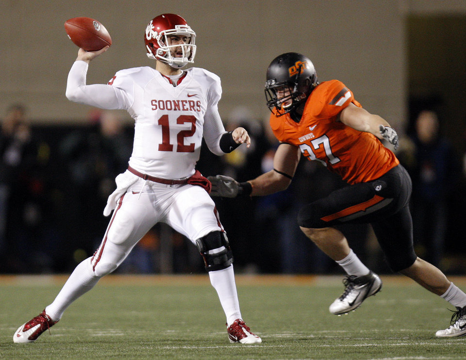 Photo - OU's Landry Jones (12) passes as he is pressured by OSU's Alex Elkins (37) during the Bedlam college football game between the Oklahoma State University Cowboys (OSU) and the University of Oklahoma Sooners (OU) at Boone Pickens Stadium in Stillwater, Okla., Saturday, Dec. 3, 2011. Photo by Nate Billings, The Oklahoman