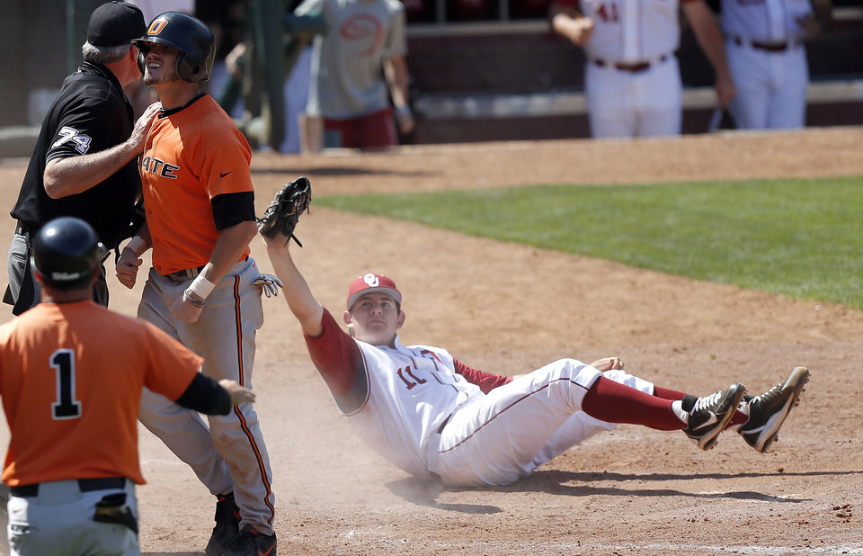 Oklahoma\'s Jacob Evans shows the home plate umpire the ball as Oklahoma State\'s Aaron Cornell celebrates during the Bedlam baseball game between the University of Oklahoma and Oklahoma State University at the Chickasaw Bricktown Ballpark in Oklahoma CIty, Sunday, May 12, 2013. Cornell was called out. Photo by Sarah Phipps, The Oklahoman