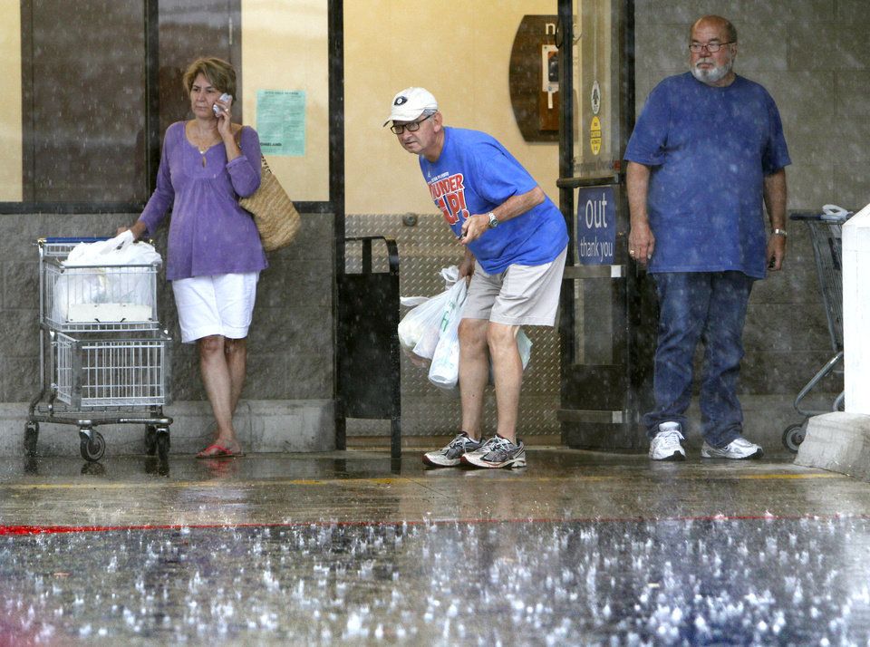 Shoppers wait for a break in a heavy downpour outside the Homeland store on North May Ave. and Britton Road in Oklahoma City, OK, Saturday, August 18, 2012,  By Paul Hellstern, The Oklahoman