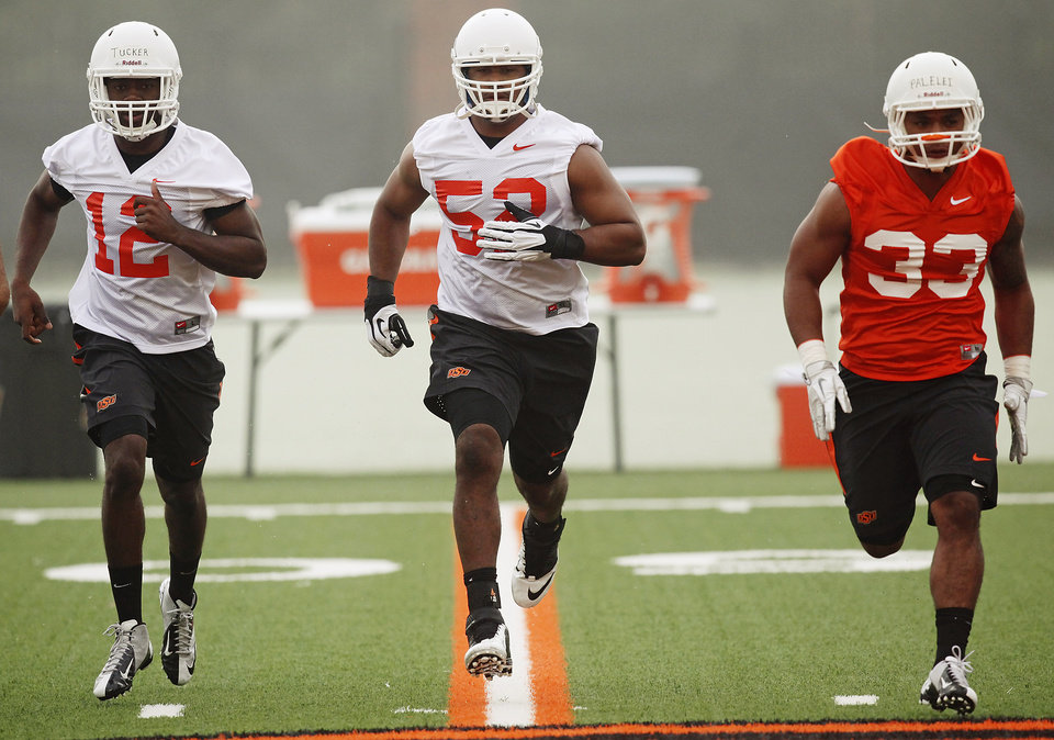 Photo - Oklahoma State players Kirk Tucker (12), Ryan Simmons (52) and Sione Palelei (33) run during the first team practice of the fall at the Sherman E. Smith Training Facility on the campus of Oklahoma State University in Stillwater on August 1, 2014. Photo by KT King, The Oklahoman