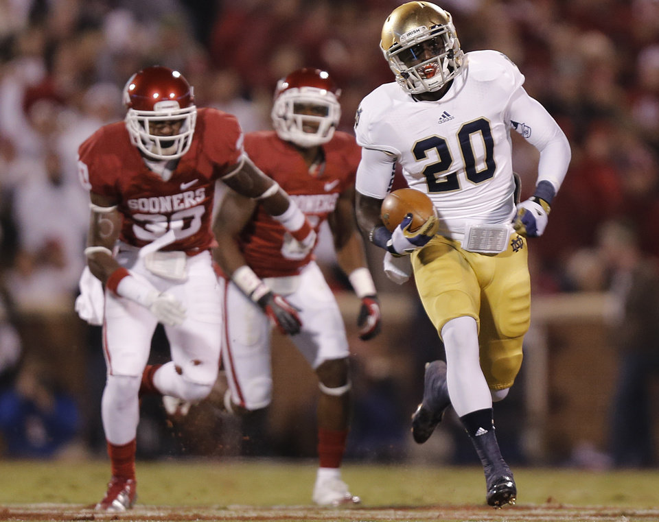 Notre Dame 's Cierre Wood (20) out runs OU's Javon Harris (30) for a touchdown  during the college football game between the University of Oklahoma Sooners (OU) and the Notre Dame Fighting Irish at the Gaylord Family-Oklahoma Memorial Stadium on Saturday, Oct. 27, 2012, in Norman, Okla. Photo by Chris Landsberger, The Oklahoman