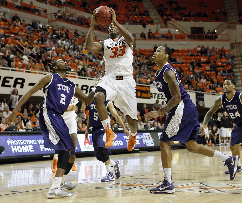 Oklahoma State's Marcus Smart (33) drives between TCU's Connell Crossland (2) and Garlon Green (33) during the college basketball game between Oklahoma State University Cowboys (OSU) and Texas Christian University Horned Frogs (TCU) at Gallagher-Iba Arena on Wednesday Jan. 9, 2013, in Stillwater, Okla.   Photo by Chris Landsberger, The Oklahoman