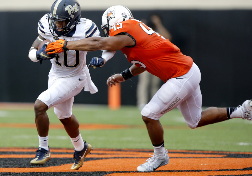 Photo - Oklahoma State's Chad Whitener (45) tries to stop Pittsburgh's Quadree Henderson (10) during a college football game between the Oklahoma State Cowboys (OSU) and the Pitt Panthers at Boone Pickens Stadium in Stillwater, Okla., Saturday, Sept. 17, 2016. Photo by Chris Landsberger, The Oklahoman