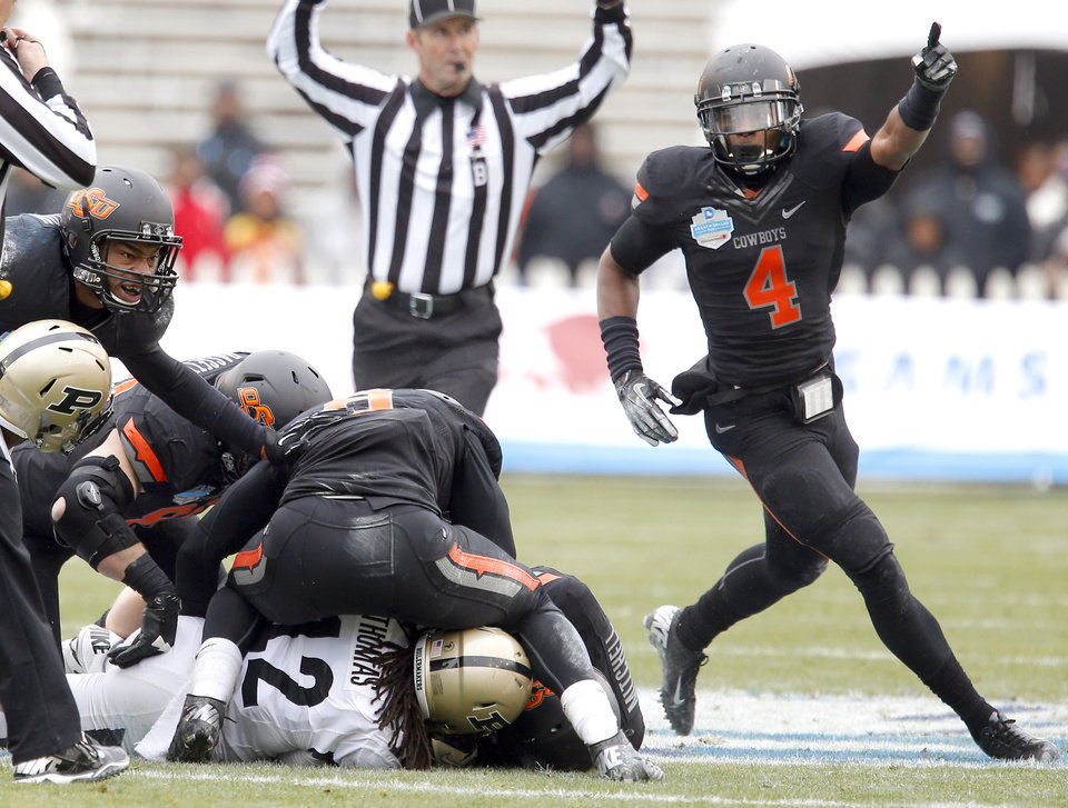 Photo - Oklahoma State's Justin Gilbert (4) celebrates a fumble recovery during the Heart of Dallas Bowl football game between the Oklahoma State University (OSU) and Purdue University at the Cotton Bowl in Dallas,  Tuesday,Jan. 1, 2013. Photo by Sarah Phipps, The Oklahoman