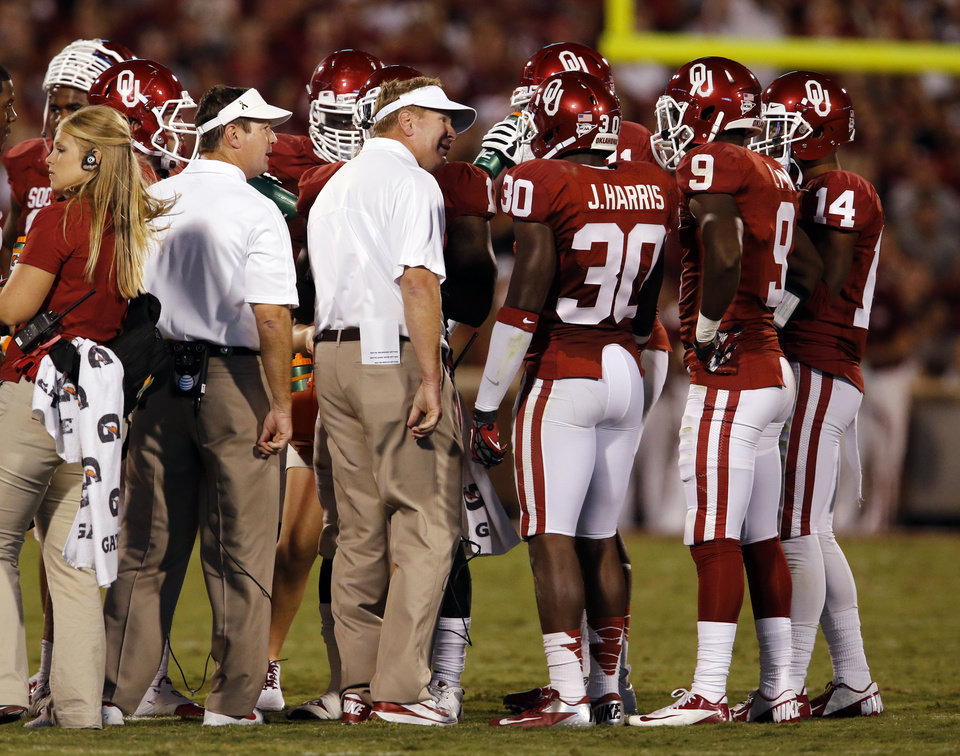 Photo - Head coach Bob Stoops and his brother Mike, defensive coordinator, talks with their defense during the second half of a college football game where the University of Oklahoma Sooners (OU) lost 24-19 to the Kansas State University Wildcats (KSU) at Gaylord Family-Oklahoma Memorial Stadium, Saturday, September 22, 2012. Photo by Steve Sisney, The Oklahoman