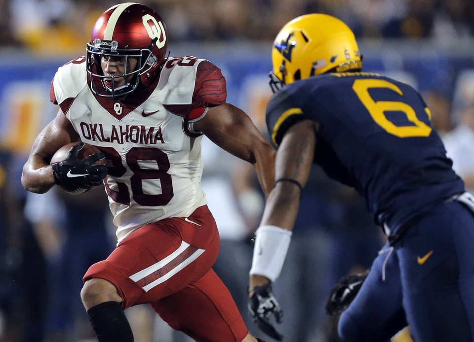 Photo - Oklahoma's Alex Ross (28) looks to get past West Virginia's Dravon Henry (6) during the college football game between West Virginia  Mountaineers and the University of Oklahoma Sooners at Milan Puskar Stadium in Morgantown, W.Va., Saturday, Sept. 20, 2014. Photo by Sarah Phipps, The Oklahoman
