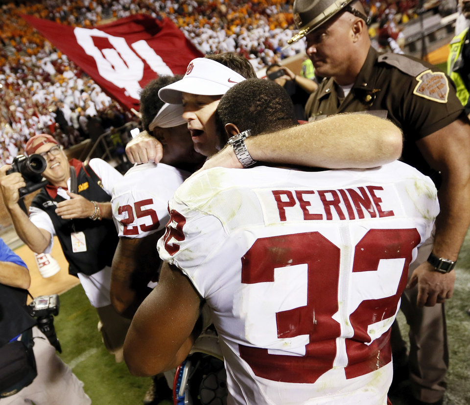 Photo - OU head coach Bob Stoops celebrates with Joe Mixon (25) and Samaje Perine (32) after the college football game between the Oklahoma Sooners (OU) and the Tennessee Volunteers at Neyland Stadium in Knoxville, Tennessee, Saturday, Sept. 12, 2015. OU won 31-24 in double overtime. Photo by Nate Billings, The Oklahoman