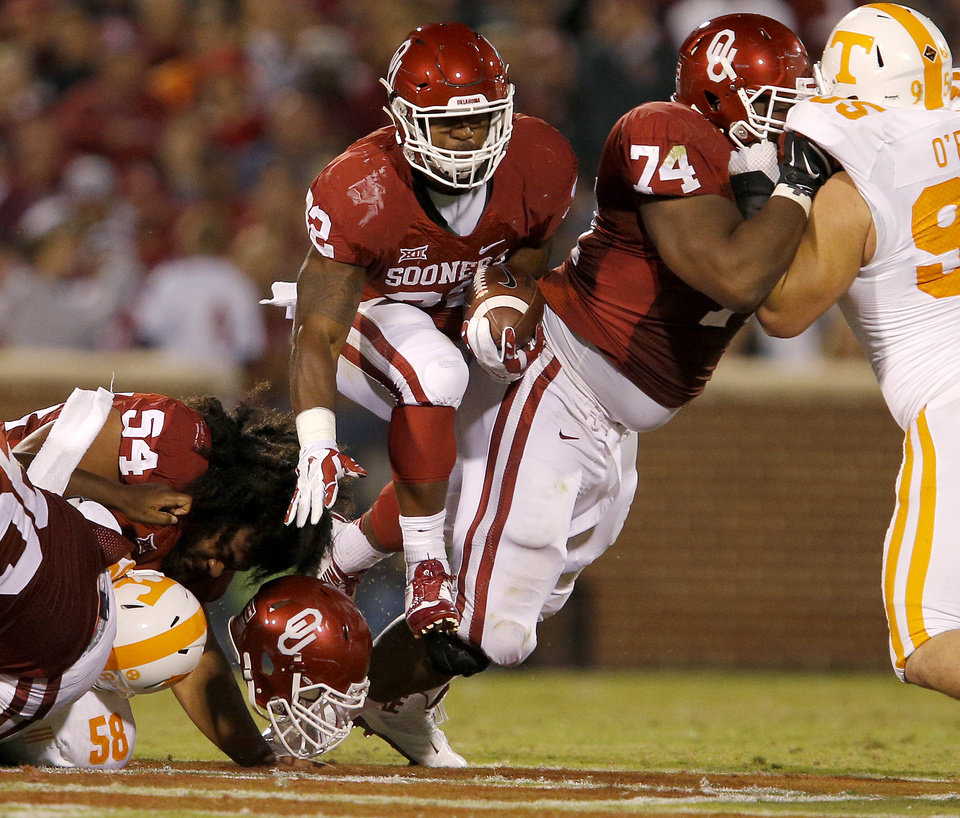 Photo - Oklahoma's Samaje Perine (32) leaps between teammates Nila Kasitati (54) and Adam Shead (74) during a college football game between the University of Oklahoma Sooners (OU) and the Tennessee Volunteers at Gaylord Family-Oklahoma Memorial Stadium in Norman, Okla., on Saturday, Sept. 13, 2014. Photo by Bryan Terry, The Oklahoman