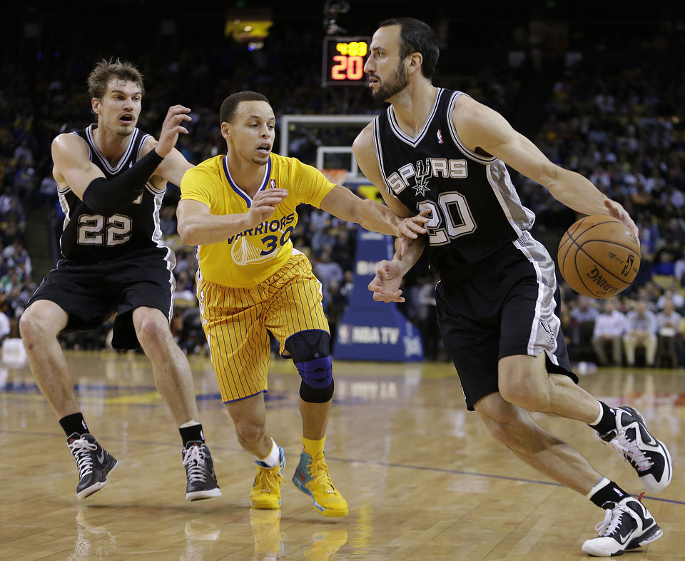 San Antonio Spurs' Manu Ginobili, right, drives the ball against Golden State Warriors' Stephen Curry (30) during the first half of an NBA basketball game Friday, Feb. 22, 2013, in Oakland, Calif. At left is Spurs' Tiago Splitter (22). (AP Photo/Ben Margot)