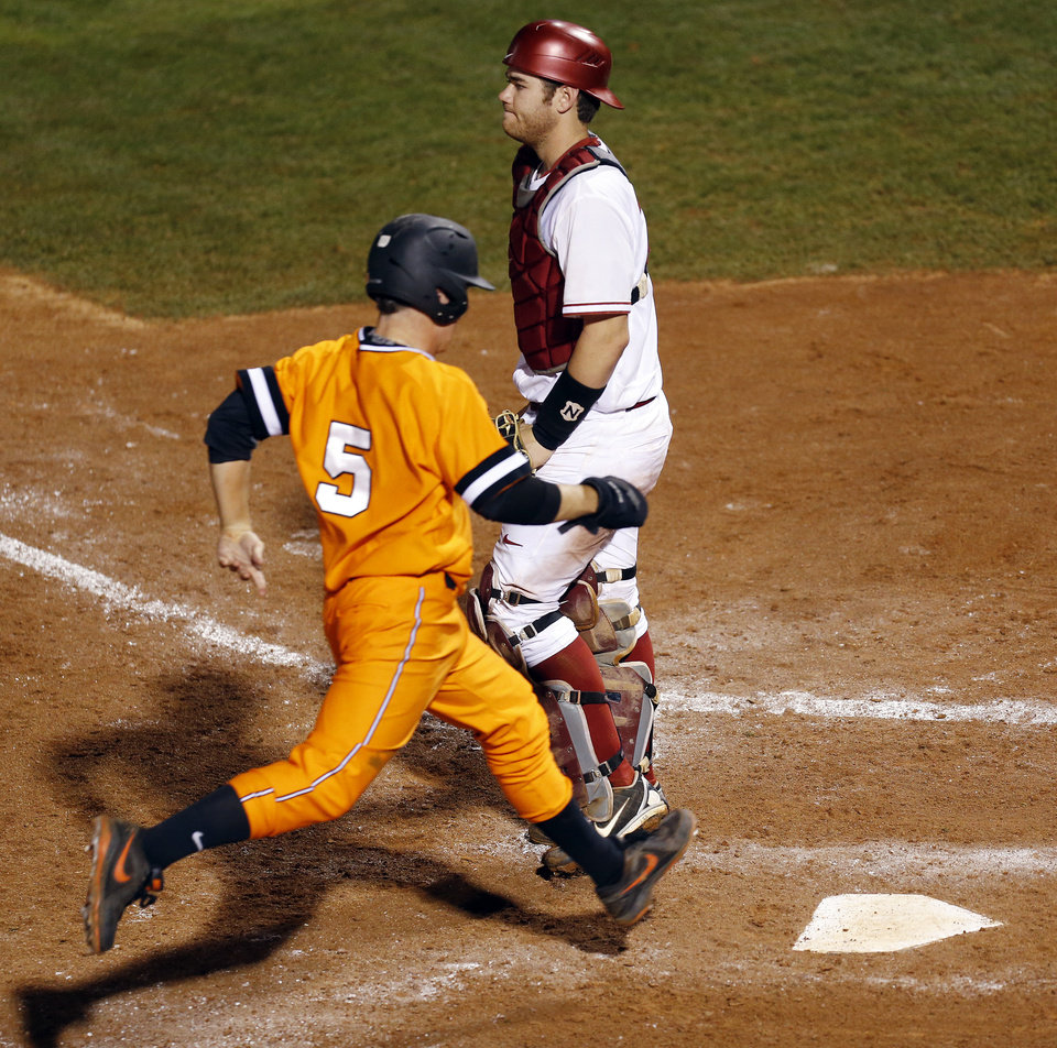Photo - OSU's Donnie Walton (5) scores past OU catcher Mac James (28) in the sixth inning during a Bedlam college baseball game between Oklahoma and Oklahoma State in the Big 12 baseball tournament at the Chickasaw Bricktown Ballpark in Oklahoma City,  Friday, May 23, 2014. Photo by Nate Billings, The Oklahoman