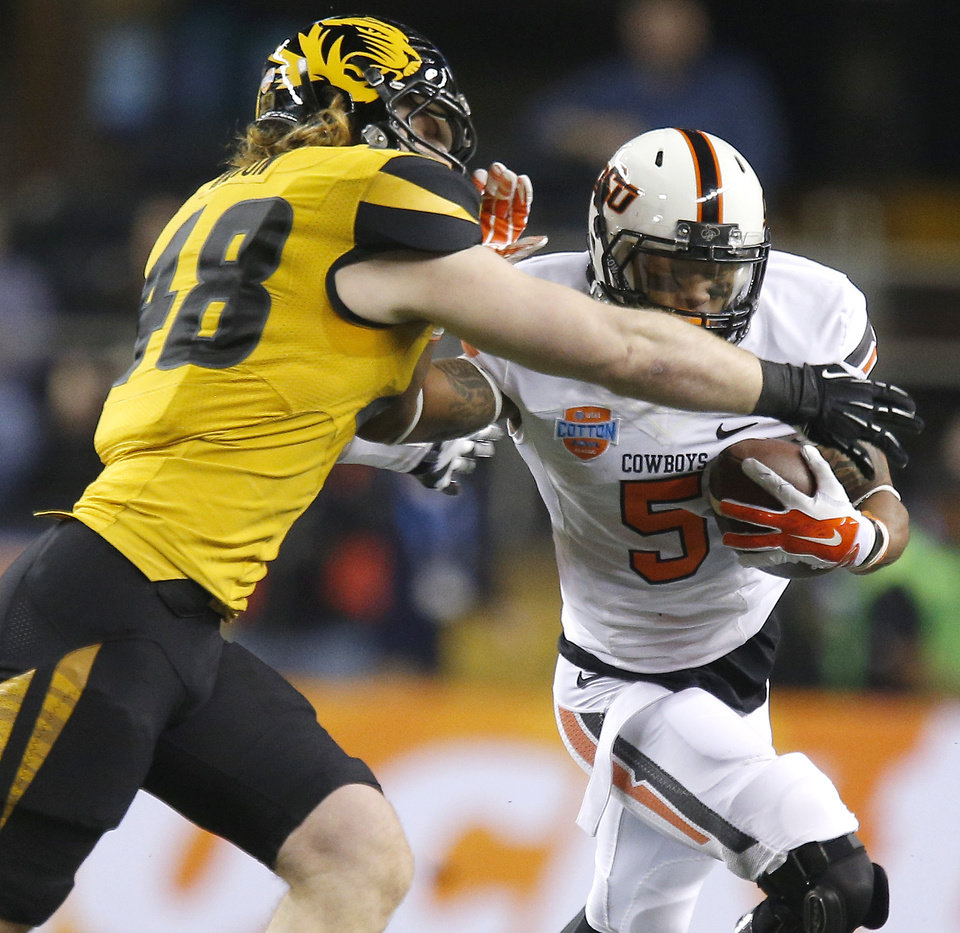 Oklahoma State's Josh Stewart (5) fights off Missouri's Andrew Wilson (48) during the AT&T Cotton Bowl Classic college football game between the Oklahoma State University Cowboys (OSU) and the University of Missouri Tigers at AT&T Stadium in Arlington, Texas, Friday, Jan. 3, 2014. Photo by Bryan Terry, The Oklahoman