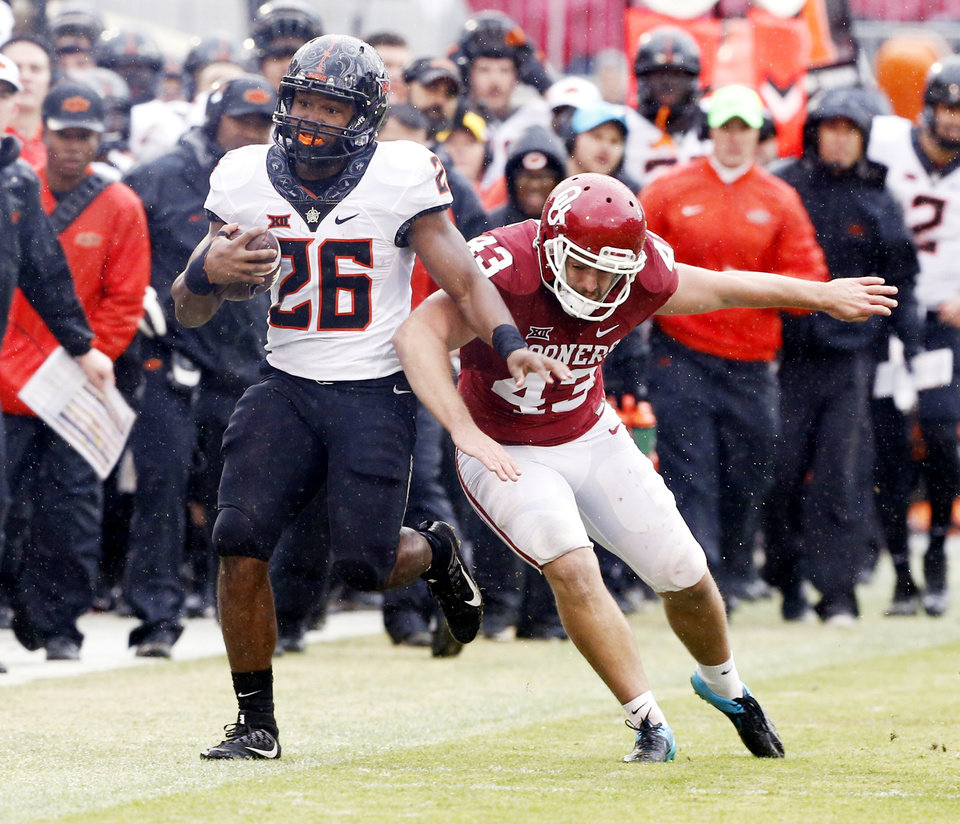 Photo - Oklahoma kicker Austin Seibert (43) pushes Oklahoma State's Barry Sanders (26) out of bounds after a long return during the second half of the Bedlam college football game between the Oklahoma Sooners (OU) and the Oklahoma State Cowboys (OSU) at Gaylord Family - Oklahoma Memorial Stadium in Norman, Okla., Saturday, Dec. 3, 2016. Photo by Steve Sisney, The Oklahoman