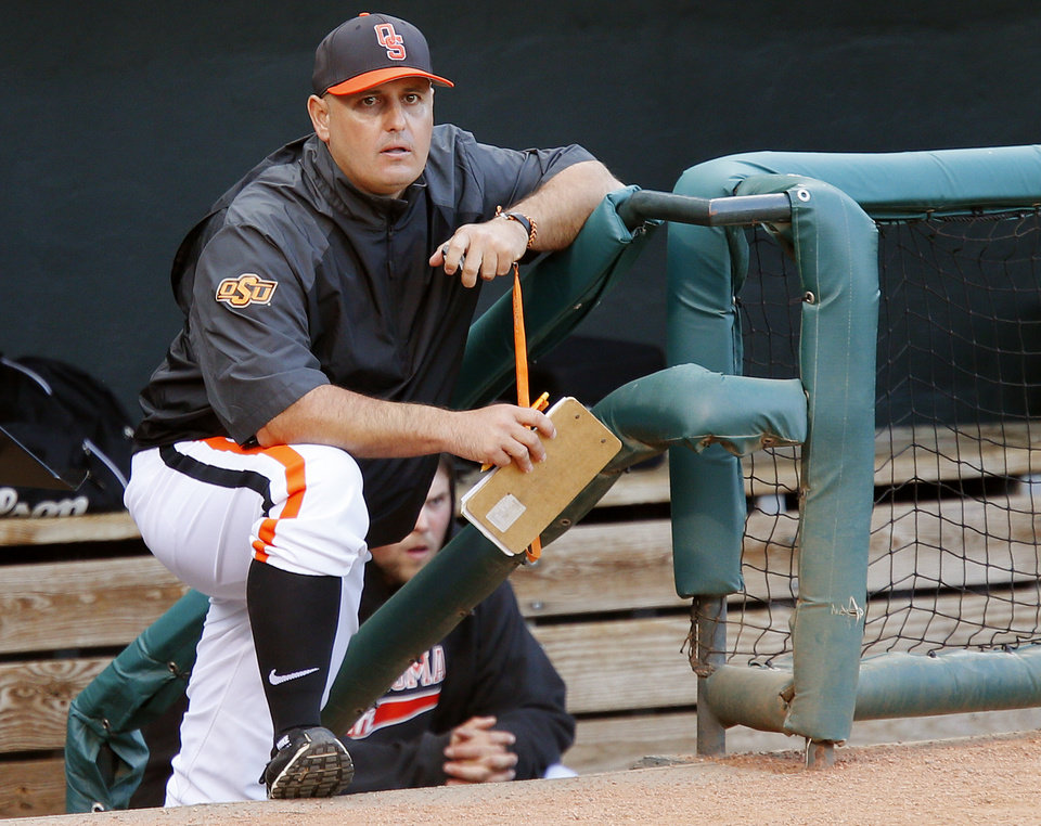 Photo - Oklahoma State coach Josh Holliday watches from the dugout during a Bedlam baseball game between the University of Oklahoma and Oklahoma State University at Chickasaw Bricktown Ballpark in Oklahoma City, Thursday, May 15, 2014. Photo by Bryan Terry, The Oklahoman