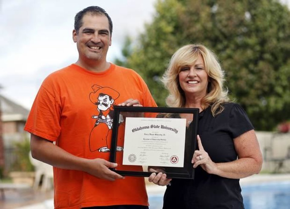Photo - Larry Mahsetky, 41, and mother Susie Carey, 58, pose for a picture with Mahsetky's diploma from Oklahoma State at Carey's house in Oklahoma City on July 31, 2014. Mahsetky recently graduated from Oklahoma State after playing football in the 1990s. Photo by KT King, The Oklahoman