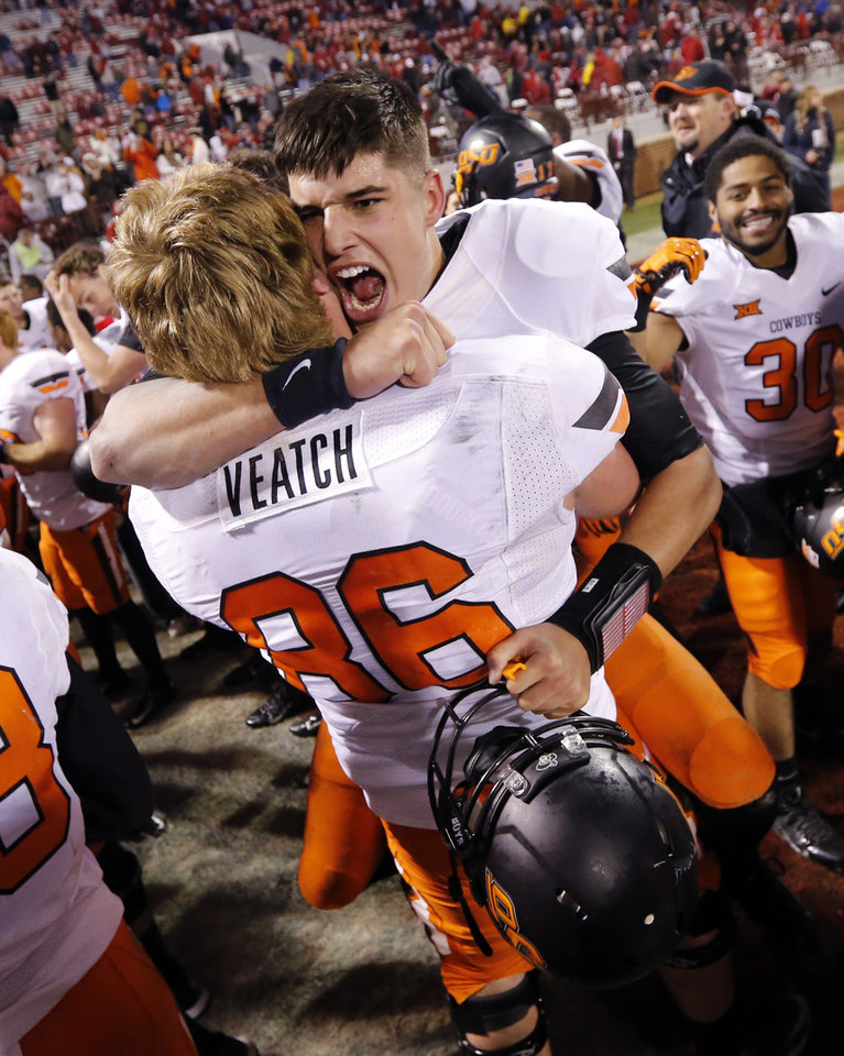 Photo - Cowboy's Mason Rudolph (10) and center Zac Veatch (50) celebrate their 38-35 victory in the Bedlam college football game between the University of Oklahoma Sooners (OU) and the Oklahoma State Cowboys (OSU) at Gaylord Family-Oklahoma Memorial Stadium in Norman, Okla., on Saturday, Dec. 6, 2014. Photo by Steve Sisney, The Oklahoman