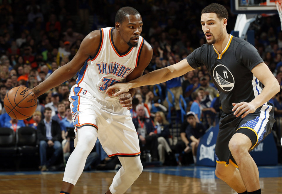 Photo - Oklahoma City's Kevin Durant (35) dribbles against Golden State's Klay Thompson (11) during an NBA basketball game between the Oklahoma City Thunder and the Golden State Warriors at Chesapeake Energy Arena in Oklahoma City, Saturday, Feb. 27, 2016. Photo by Nate Billings, The Oklahoman