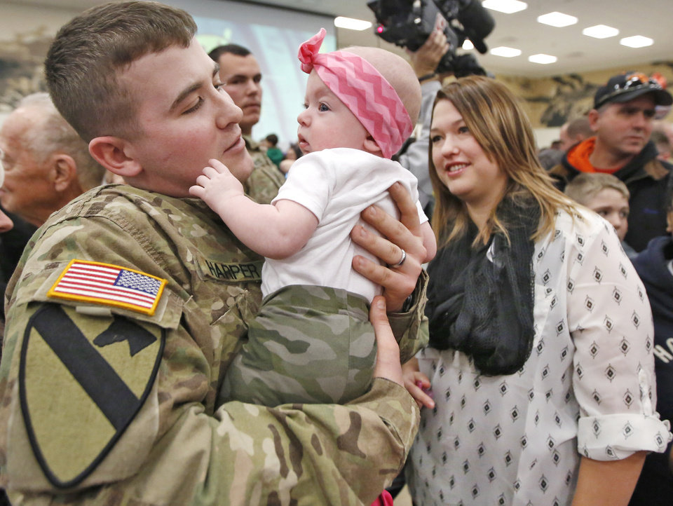 Photo -  Spc. Justin Harper meets his daughter, Paisley, 4 months, for the first time, as his wife, Meagan Harper, watches Friday during an Oklahoma Army National Guard homecoming ceremony for Battery B, 1st Battalion, 158th Field Artillery, 45th Field Artillery Brigade in Mustang. The guardsman were returning from deployment to Afghanistan in support of Operation Enduring Freedom. Photo By Steve Gooch, The Oklahoman   Steve Gooch -