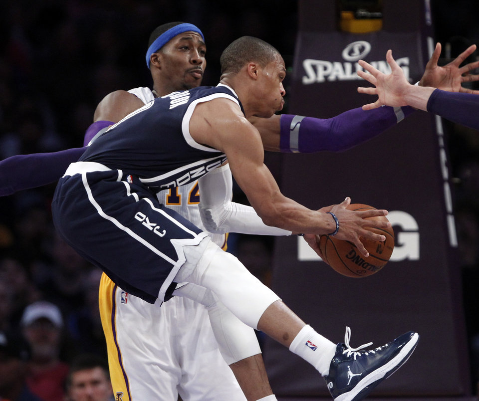 Oklahoma City Thunder guard Russell Westbrook,front, passes as Los Angeles Lakers center Dwight Howard (12) defends in the first half of an NBA basketball game in Los Angeles Sunday, Jan. 27, 2013. (AP Photo/Reed Saxon)  ORG XMIT: LAS102
