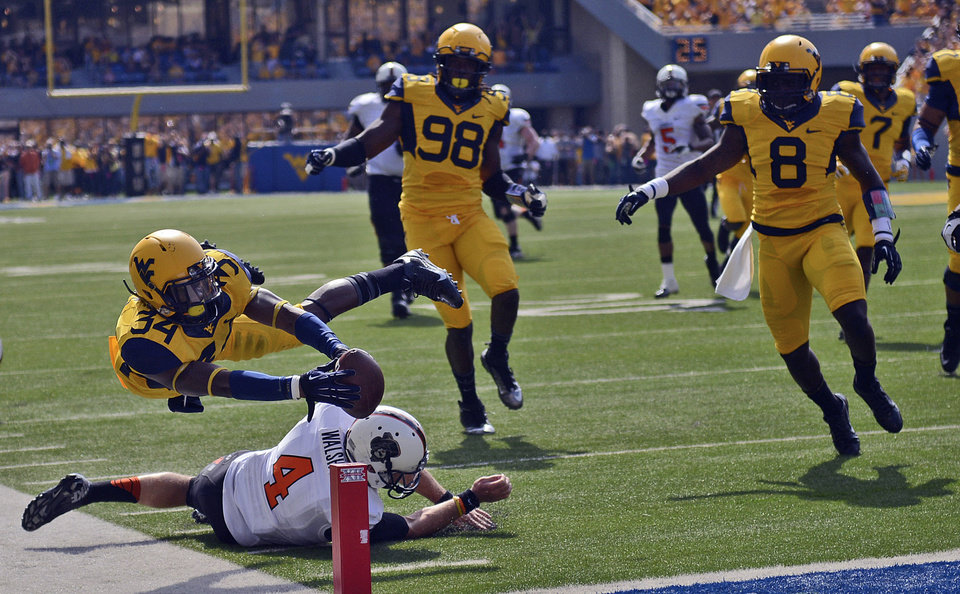 Photo - West Virginia' Ishmael Banks (34) reaches over the goal line for touchdown after returning an interction 58-yard for the score during the first quarter of an NCAA college football game Oklahoma State in Morgantown, W.Va., on Saturday, Sept. 28, 2013. (AP Photo/Tyler Evert)