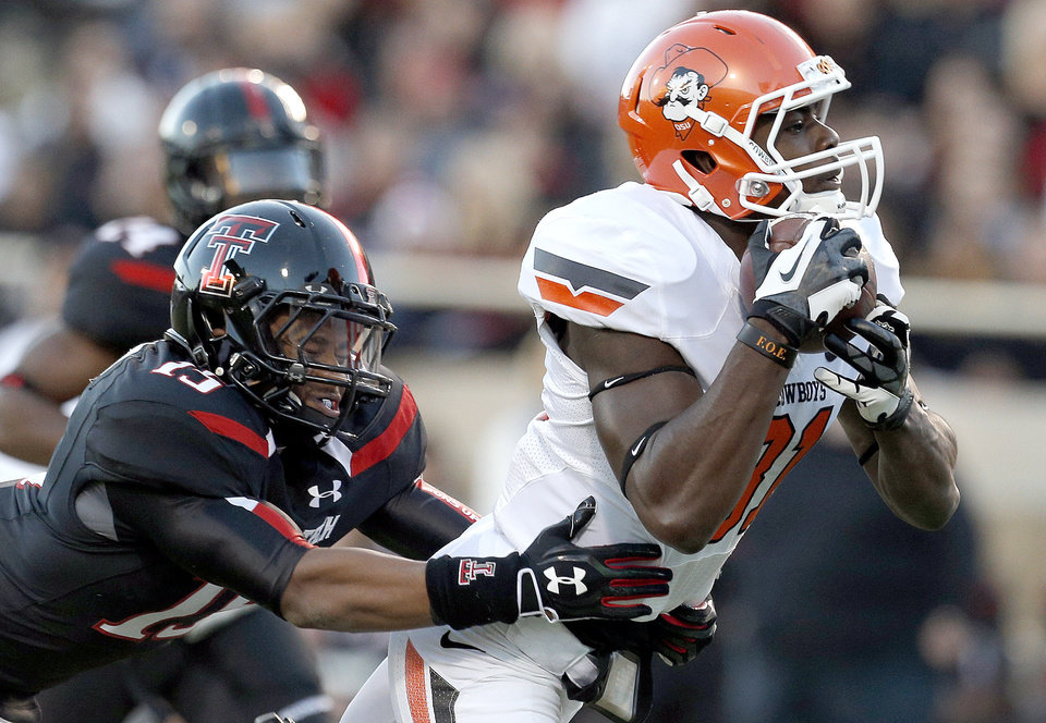 Oklahoma State \'s Jhajuan Seales (81) makes a catch as Texas Tech\'s Keenon Ward (15) defends during the college football game between the Oklahoma State Cowboys (OSU) and the Texas Tech Red Raiders (TTU) at Jones AT&T Stadium in Lubbock, Texas, Saturday, Nov. 2, 2013. Photo by Sarah Phipps, The Oklahoman