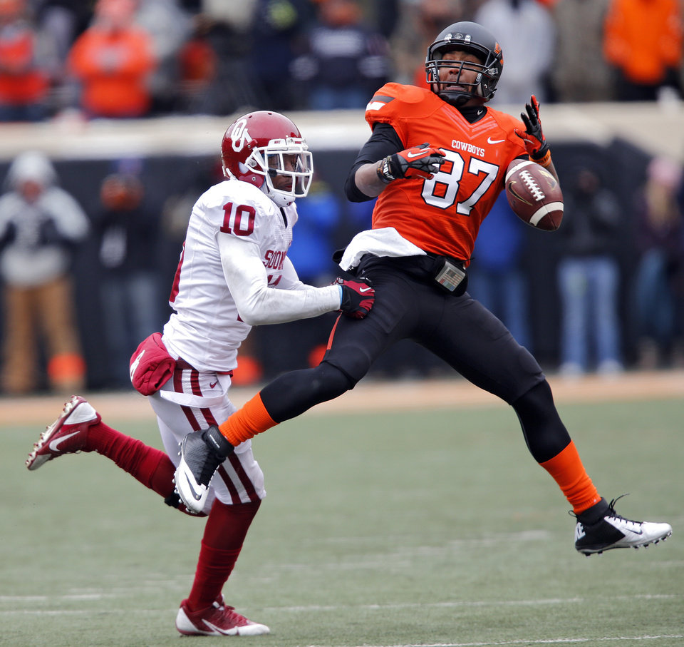 Photo - Oklahoma State's Tracy Moore (87) drops a pass in front of Oklahoma's Quentin Hayes (10) during the Bedlam college football game between the Oklahoma State University Cowboys (OSU) and the University of Oklahoma Sooners (OU) at Boone Pickens Stadium in Stillwater, Okla., Saturday, Dec. 7, 2013. Photo by Chris Landsberger, The Oklahoman