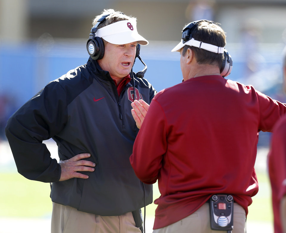 Photo - Oklahoma defensive coordinator Mike Stoops talks with coach Bob Stoops during the college football game between the University of Oklahoma Sooners (OU) and the University of Kansas Jayhawks (KU) at Memorial Stadium in Lawrence, Kan., Saturday, Oct. 19, 2013. Oklahoma won 34-19. Photo by Bryan Terry, The Oklahoman